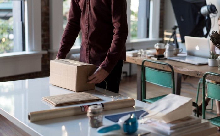 how to ship your products man with packaged box How to Ship Your Products During the Coronavirus Pandemic