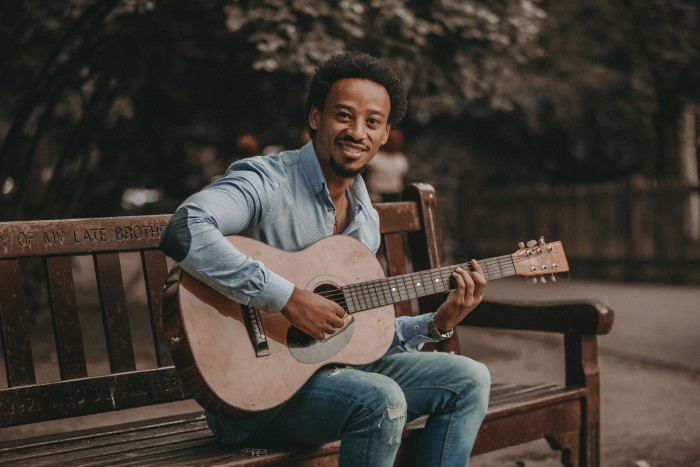 A man holding a guitar sits on a park bench and smiles at the camera