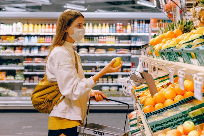 A person wearing a surgical mask holds a lemon while looking at produce in a grocery store.