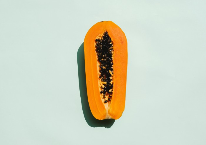 Overhead view of half a papaya against a teal background.