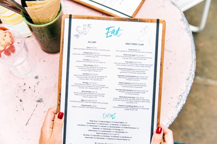 Closeup of hands with painted finger nails holding a brunch menu over a table..