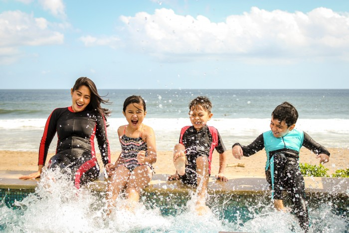 Three children and an adult laugh and splash their feet in a pool by the ocean.
